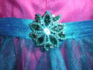 Teal top-stitching and Swarovski pin.