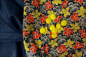Vintage floral print cotton fabric with bright red, lemon yellow and pale blue violets on a dark blue background.