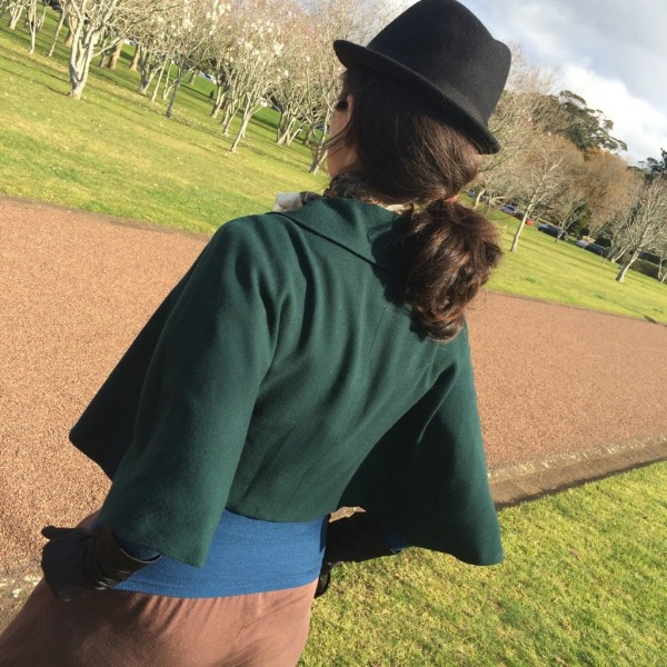 green cape standing back 2